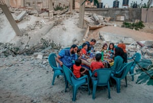 A Palestinian family break their fast next to their house that was destroyed during the two-day escalation in Rafah