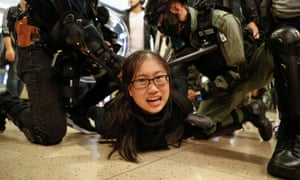 Police officers detain a protester during a demonstration inside a shopping centre.
