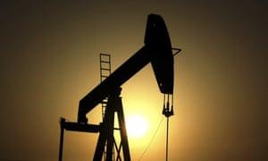 Sun sets behind an oil pump in the desert oil fields of Sakhir, Bahrain.