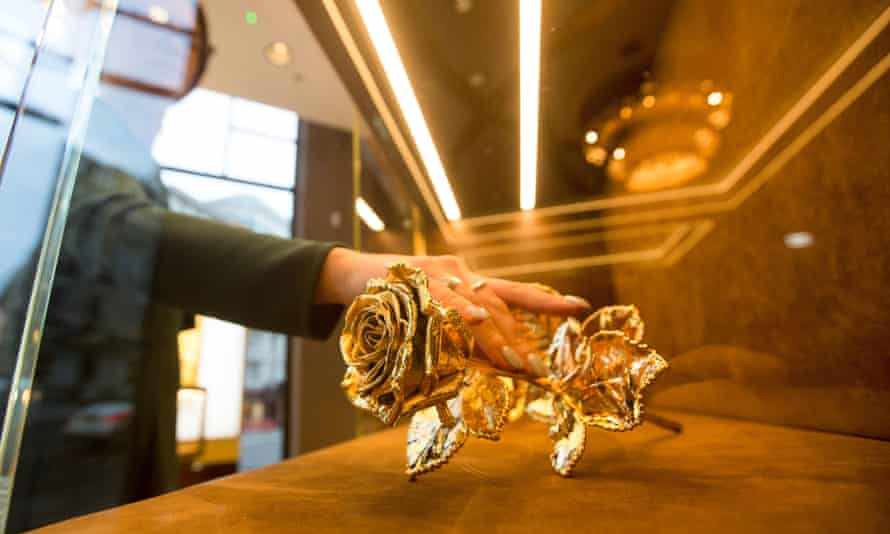 An employee inspects a golden rose on display at Sharps Pixley showroom in London