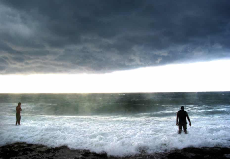 Two men watch the heavy swell and overcast skies at a western beach in Havana, after Hurricane Frances passed over Florida, 90 miles from the Cuban coast.
