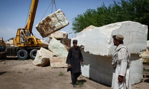 Workers move large blocks of marble