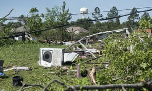 Household items and debris are scattered along land between houses in Lindale, Texas, after severe weather including flooding and a possible tornado hit the region.