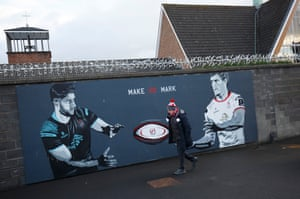 An Ulster fan walks past a mural before the Ulster v Racing 92 European Champions Cup group-stage match at the Kingspan Stadium in Belfast.