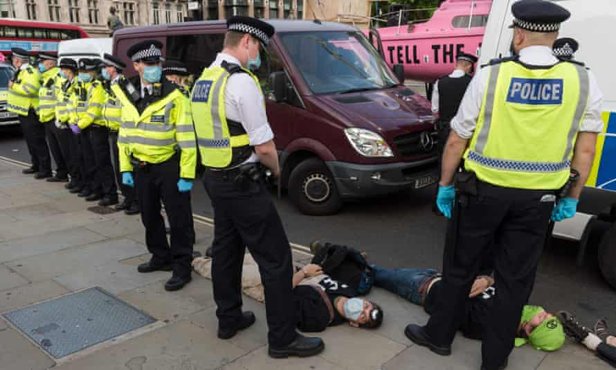 Activists from Extinction Rebellion lie on the ground after being arrested in Parliament Square following a march through central London on 10 September 2020.
