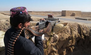 An Afghan local police officer keeping watch during an ongoing battle with Taliban militants.