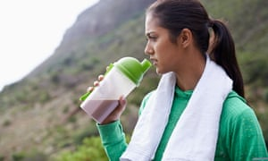 Young woman drinks protein shake.