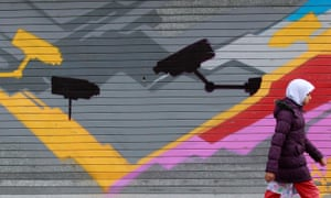 A girl walks past graffiti showing CCTV cameras in the Sparkbrook area of Birmingham, England