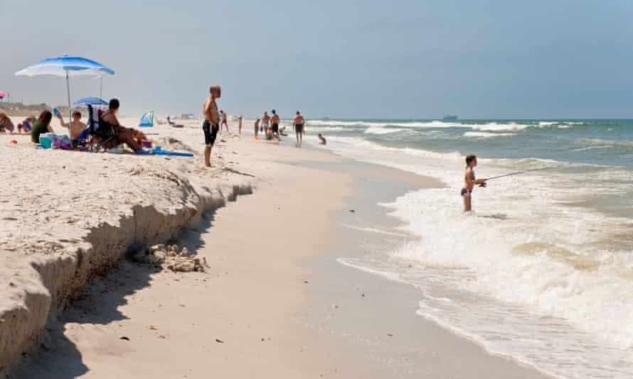 Family playing on white sand beach at St Joseph Peninsula state park.