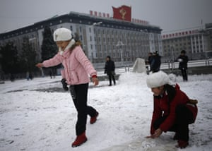 Pyongyang, North Korea: Girls play in snow on Kim Il-sung square