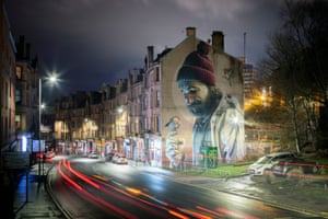 A giant mural on the gable end of a terraced house, depicting a bearded man in a bobble hat looking at a bird perched on his hand