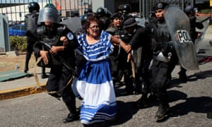 Riot police detain an anti-government protester in traditional costume.