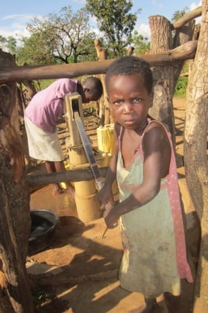 A girl pumps water at the Obalanga borehole in Katine