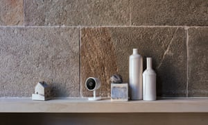 The Nest Cam IQ sits on a shelf next to some things.