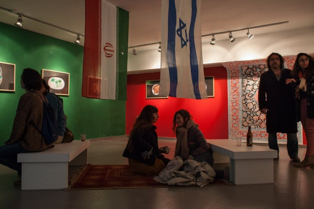Two young women sit on a Persian rug beneath an Israeli flag and an Iranian one bearing the emblem of the Islamic Republic, at the opening of the Iranian embassy of culture in Jerusalem on 21 December 2015.