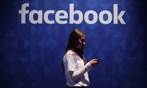 A woman using her phone under a Facebook logo