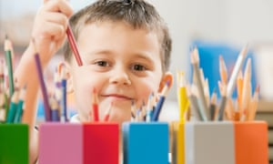 Child picking up a coloured pencil