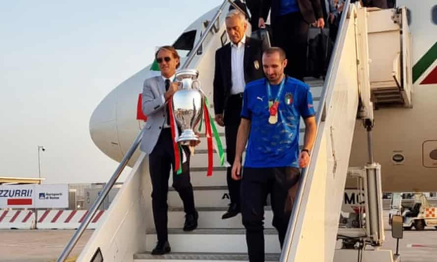 Roberto Mancini takes the trophy out of the plane