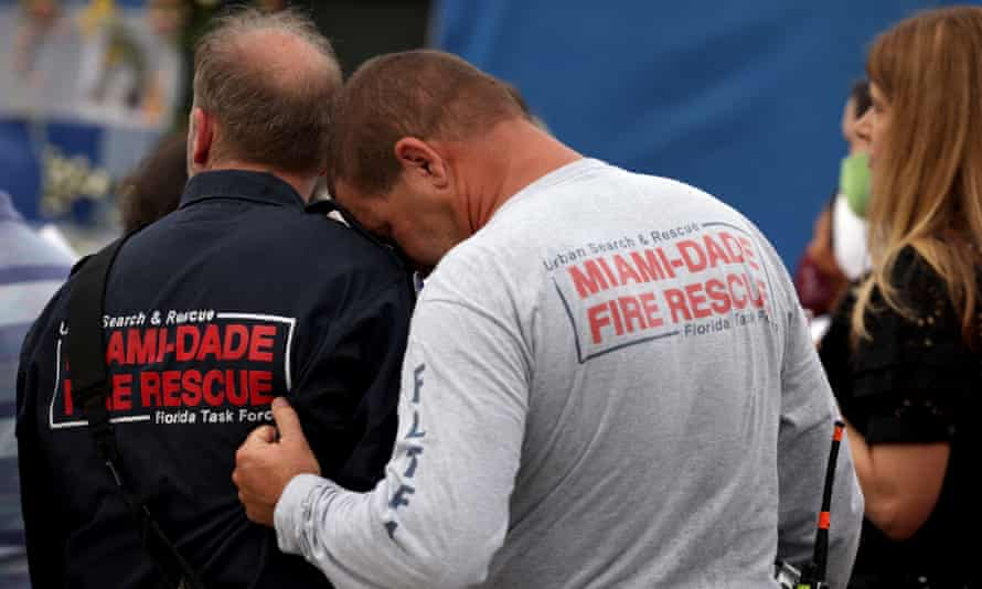 Rescue workers embrace after a moment of silence near the memorial site for victims in Surfside, Florida.