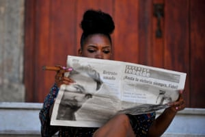 A woman smokes a cigar as she reads the newspaper