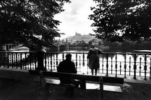 A couple on Charles Bridge look out over the Vltava river towards Prague Castle.