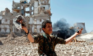 A Huthi rebel inspects bomb damage in Sana'a, Yemen.