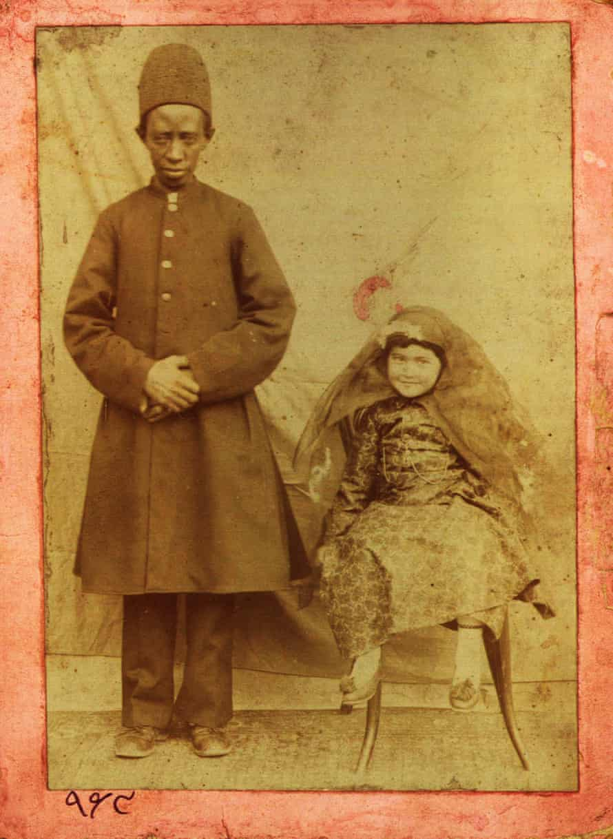 A young aristocrat posing next to her personal African eunuch.