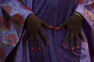 A model with bright orange nail polish poses with her hands on a purple   outfit