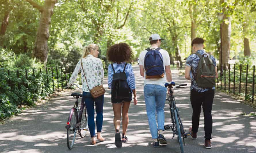 Friends walking with bicycles in parkGettyImages-595347273