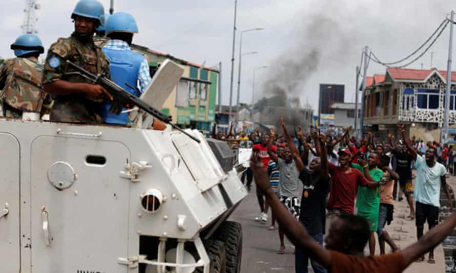 Residents chant slogans against the president as UN peacekeepers patrol during unrest in the streets of the capital, Kinshasa