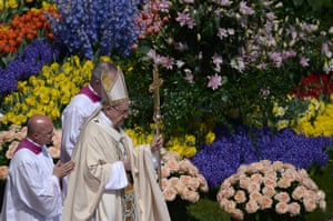 Pope Francis walks past flowers adorning the altar during the Easter Sunday mass