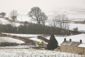 An ambulance makes its way down a country lane in the snow covered countryside near Bellerby