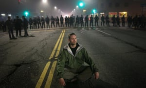 A man sits in the street after being blocked by a line of police officers in Staten Island, New York.