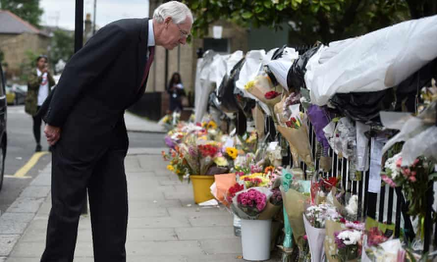 Martin Moore-Bick examines floral tributes after the Grenfell tower fire