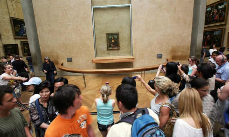 People visiting the Louvre in Paris take pictures of the portrait of Mona Lisa by Leonardo da Vinci