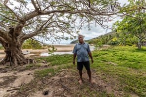 Josateki Manatua stands in front of the advancing coastline in Raviravi village, Fiji