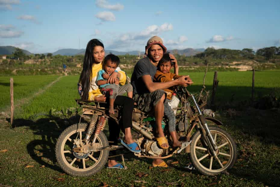 Mother, Nu, and father, Trun, with their sons, Khun 6, and A Kinh, 3, on the family's motorcycle, in front of their rice field in Gia Lai, in the Central Highlands, Vietnam.