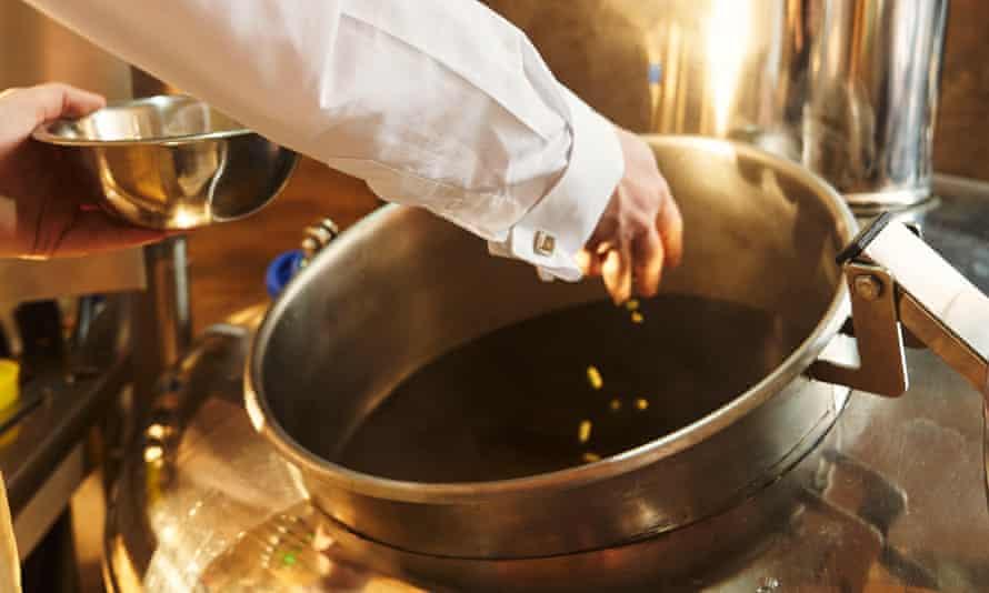 A brewer adding wort to a brewing kettle