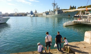 Family at Muelle Uno, quay in the port of Malaga, with two warships in background, Andalusia, Spain.