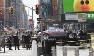 A car rests on a security barrier in New York's Times Square after driving through a crowd of pedestrians Thursday.