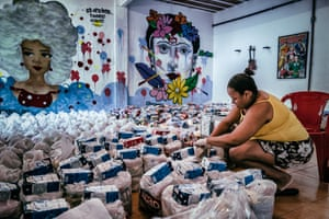 Volunteers prepare 'cestas basicas' (bags of basic necessities such as rice, beans, sugar) to distribute for the vulnerable and elderly in the City of God favela