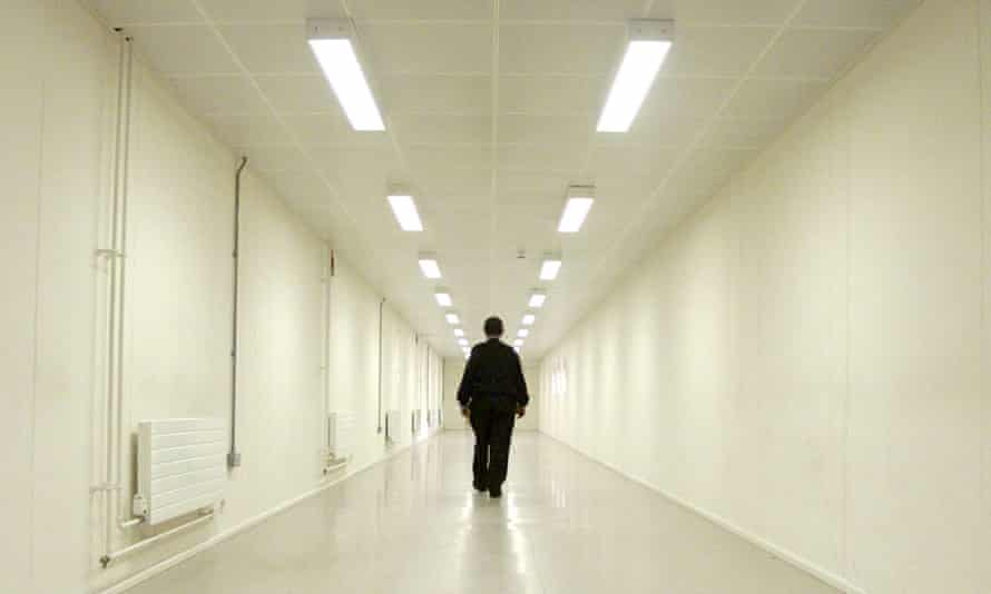 A security officer patrols a corridor in an immigration removal centre.