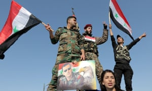 Syrian soldiers and civilians wave national flags during a gathering in Umayyad square in Damascus