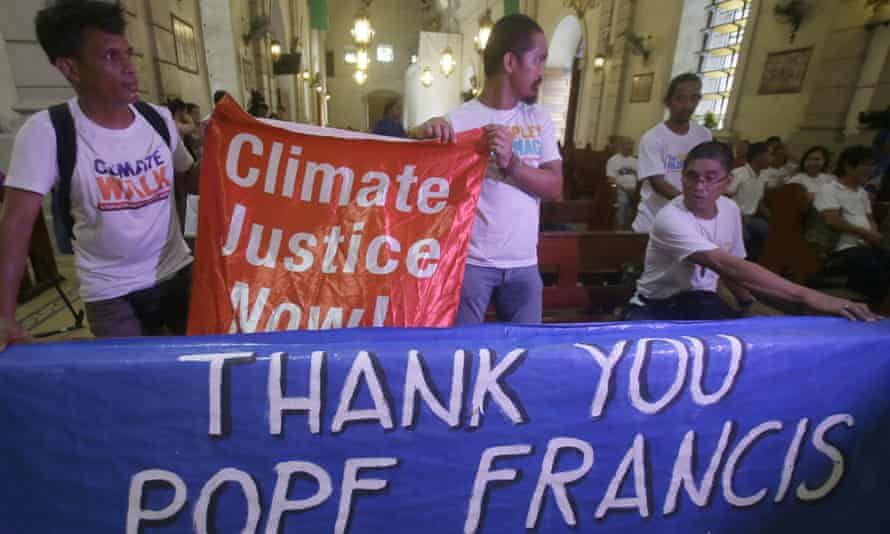 Environmental activists prepare to listen to speeches to coincide with Pope Francis' encyclical on climate change.
