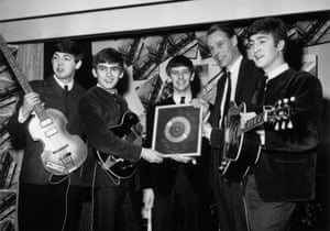 (L-R) Paul McCartney, George Harrison, Ringo Starr, George Martin and John Lennon hold up the Beatles' first silver disc in 1963, marking sales of more than 250,000 copies of single Please Please Me. Starr famously joined the band in 1962 after Martin let it be known that he believed the Beatles' then drummer, Pete Best, was not up to scratch.