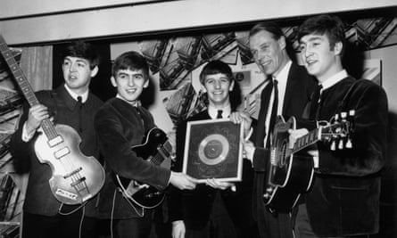 Paul McCartney, George Harrison, Ringo Starr, producer George Martin and John Lennon show off a silver disc in 1963.