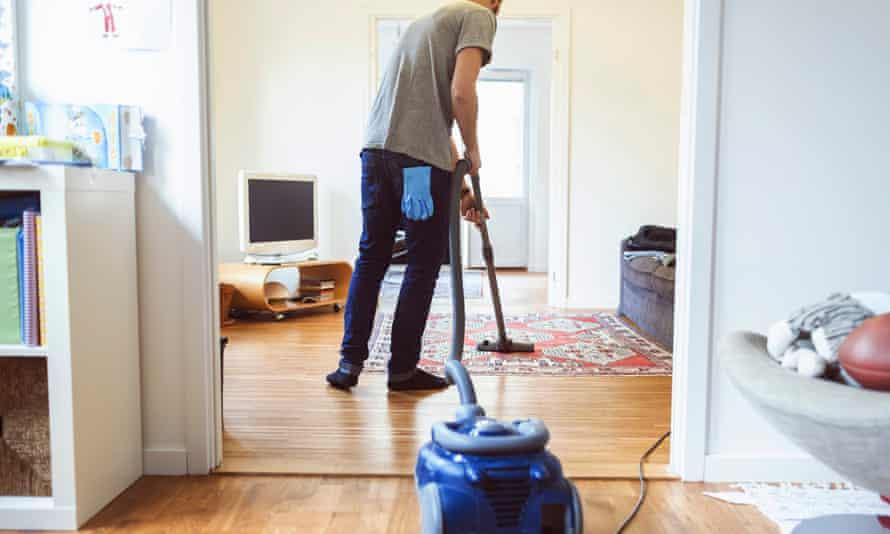 Rear view of man vacuuming