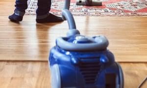 Rear view of man vacuuming carpet
