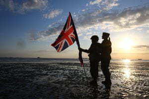 Re-enactors carry a union flag on the beach in Arromanches