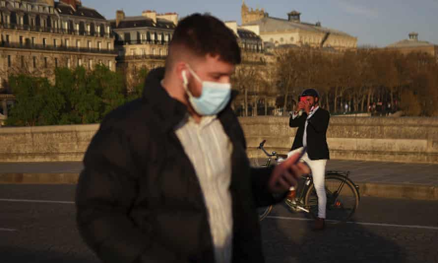 A man wears a face mask while walking in Paris, France